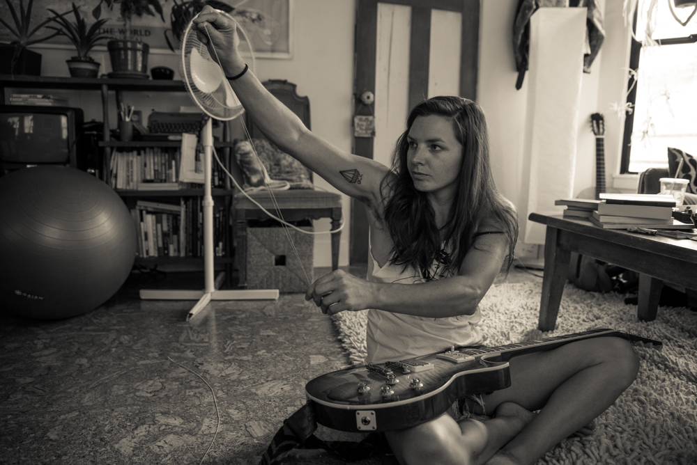 Whitney restrings her guitar. (Photo by Christine Mitchell)